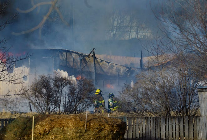 Firefighters respond to a burning trailer home on 26th Street NW on Tuesday afternoon.