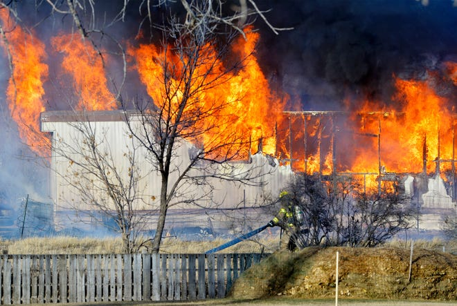 Flames engulf a trailer home on the 200 block of 26th Street NW, Tuesday afternoon.