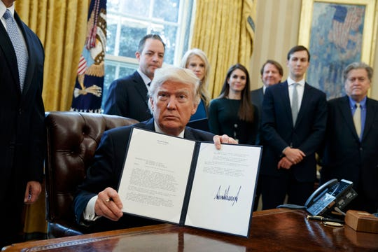 FILE - In this Jan. 24, 2017 file photo, President Donald Trump shows his signature on an executive order on the Keystone XL pipeline in the Oval Office of the White House in Washington. Justice Department attorneys and the Canadian company behind the proposed Keystone XL oil pipeline say the U.S. government shutdown shouldn't delay a court hearing on a judge's decision to halt construction. Justice Department attorney Bridget McNeil said in a court filing Monday, Jan. 7, 2019, that federal attorneys' participation in the hearing next Monday in U.S. District Court in Great Falls isn't necessary. (AP Photo/Evan Vucci, File)