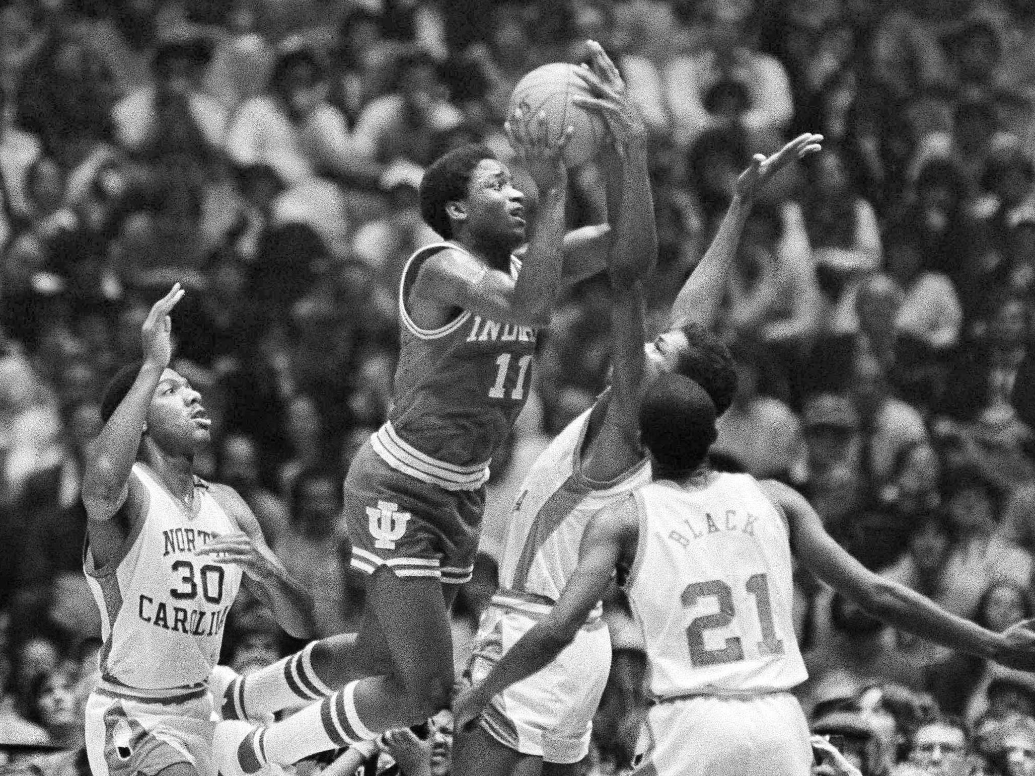 Indiana's Isiah Thomas uses jump shot over up stretched arms of University of North Carolina's Sam Perkins, as Jimmy Black (21) watches on Monday, March 31, 1981 in title game of NCAA championship in Philadelphia. Indiana won the NCAA crown by beating the Tar Heels, 63-50, and Thomas was selected the most valuable player.