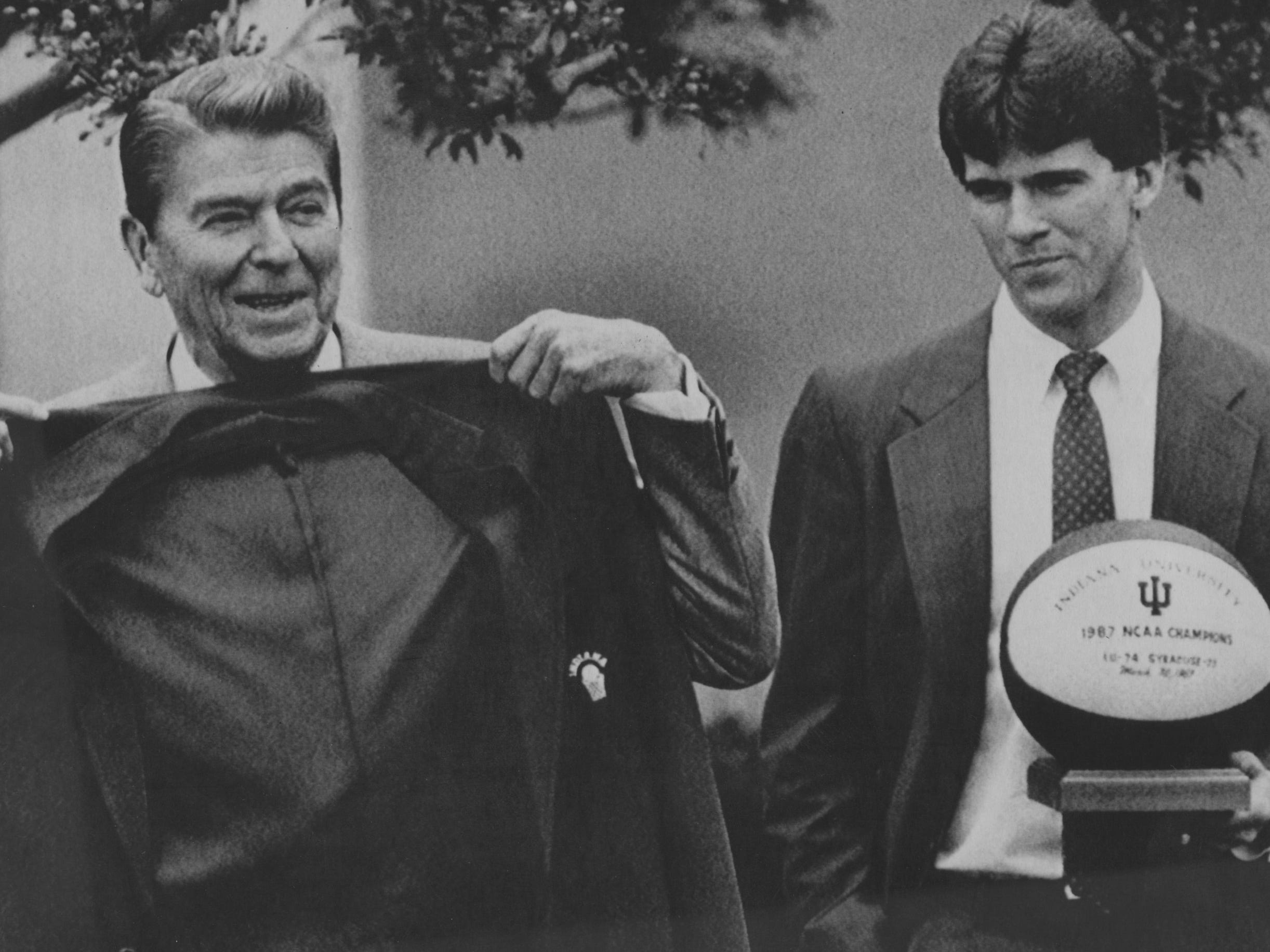President Ronald Reagan holds up a red blazer that was presented to him by members of the Indiana University basketball team during a White House Rose Garden ceremony Friday. Indiana's Steve Alford holds a basketball trophy at right. Regan welcomed the Hoosiers to the White House after they won the 1987 NCAA men's basketball championship.
