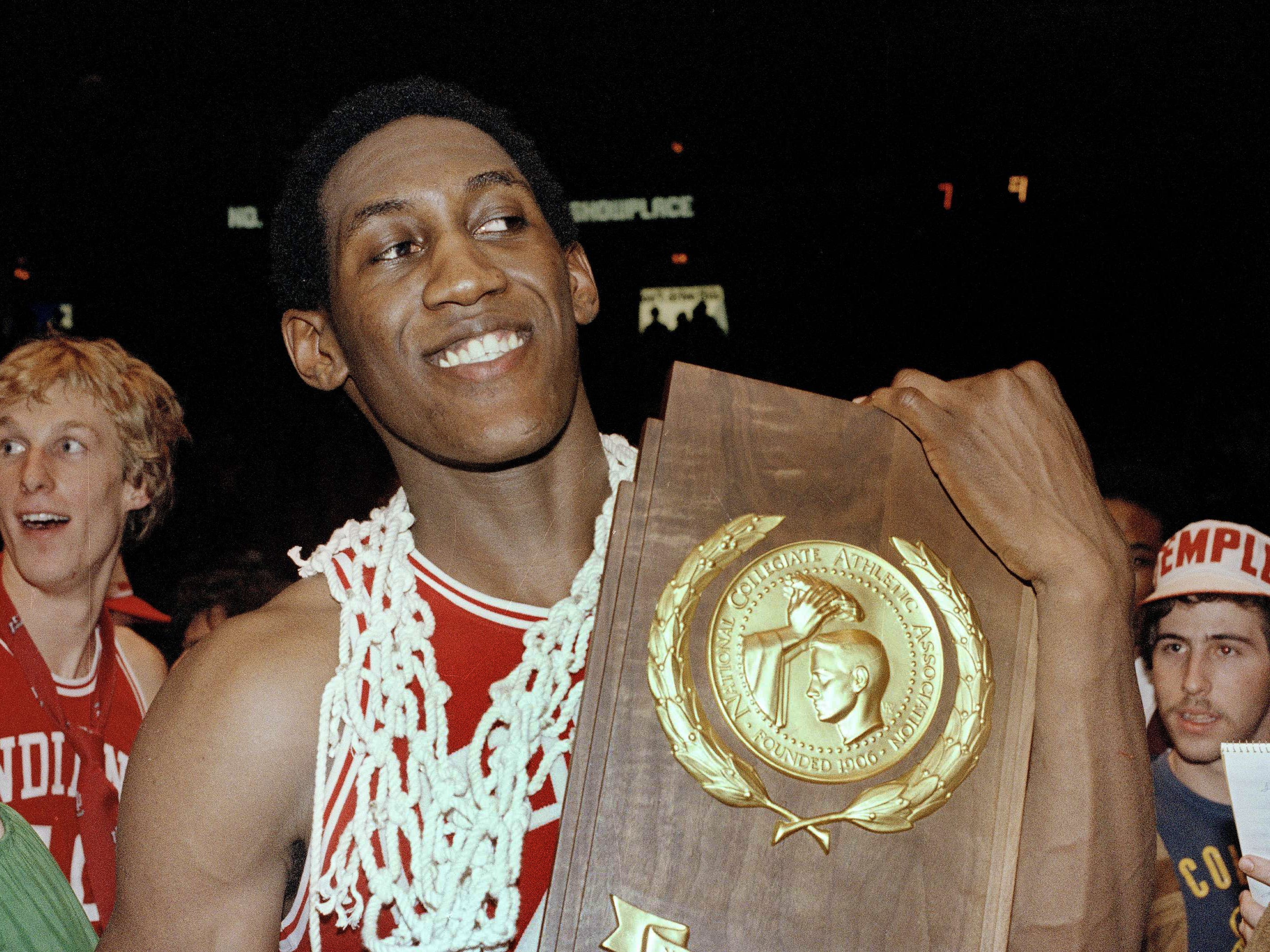 Isiah Thomas of Indiana University wears the net from the basket around his neck and holds plaque after his team won over North Carolina, 63-50, in the final NCAA championship game, March 31, 1981. Thomas was declared MVP of the game in Philadelphia.