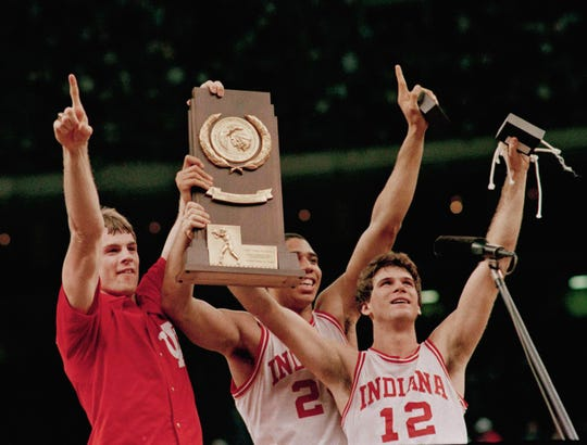 Indiana players Todd Meier, Daryl Thomas and Steve Alford raise the trophy high after the Hoosiers won the NCAA Championship by defeating Syracuse, 74-73, Monday night March 31, 1987.