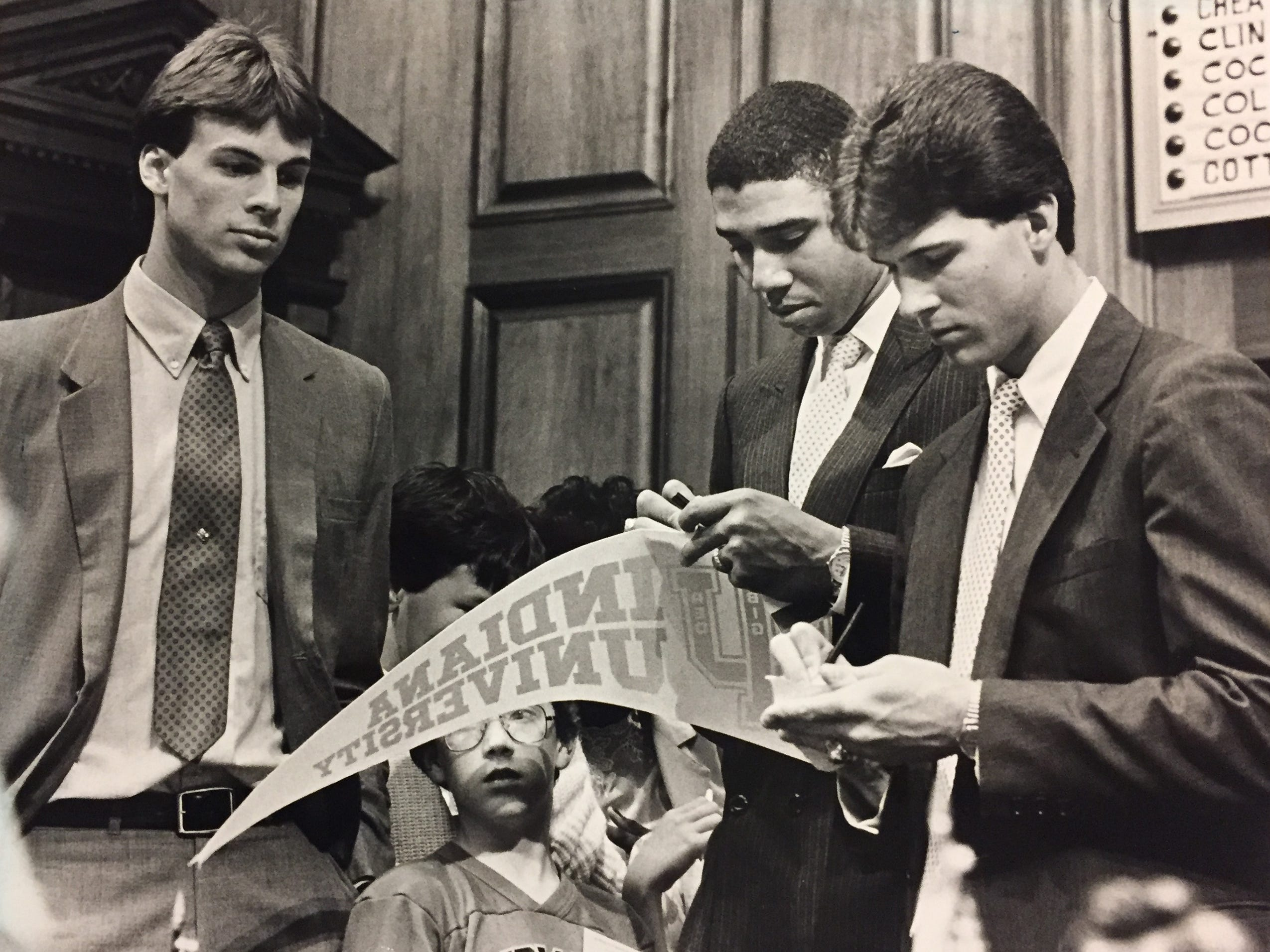 Todd Meier (left), Daryl Thomas and Steve Alford (right) sign pennant for Todd Dovrak, 9, during House visit in April 1987.