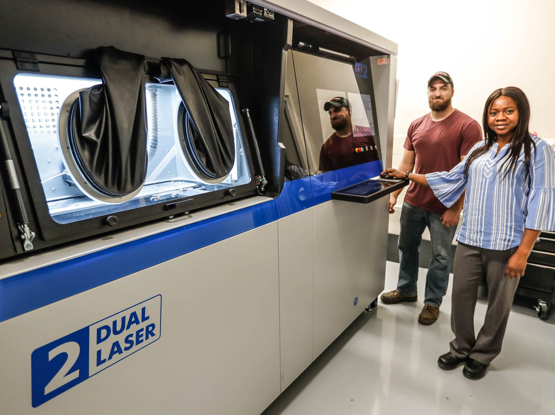 Experimental Mechanist, Darren Brown, left, and Senior Additive Manufacturing Engineer, Adeola Olubamiji, stand by a 3-D-printer in the Cummins Technical Center, 1900 McKinley Ave, Columbus, Ind., on Monday, Jan. 7, 2018.