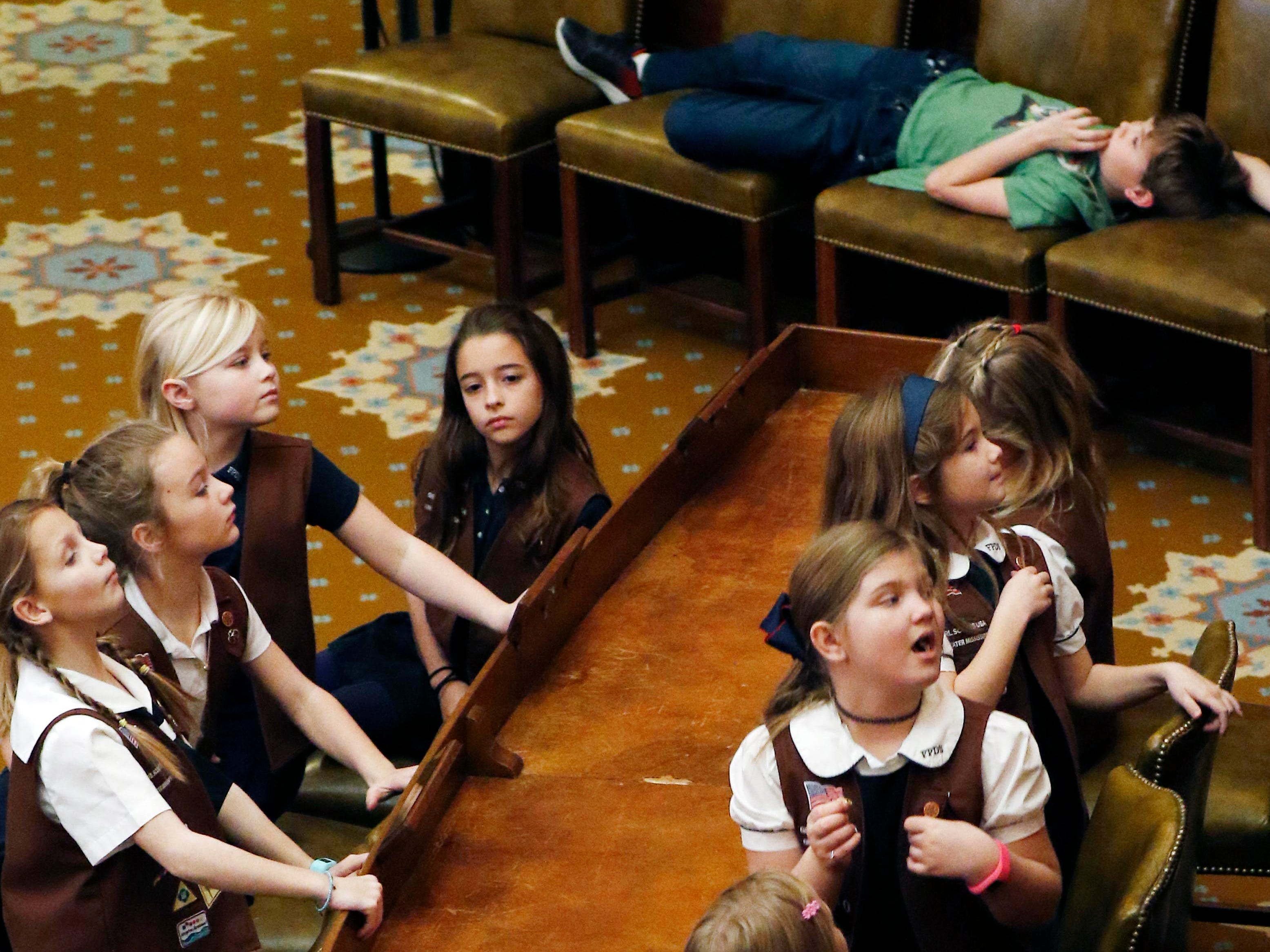 Members of Girl Scout Troop 3980 look toward the speaker's podium while George Colin, 10, an older brother to one of the Scouts, pretends to take a nap in the House chamber at the Capitol in Jackson, Miss., Monday, Jan. 7, 2019. The troop of mainly second graders, based at First Presbyterian Day School, toured the Capitol prior to Tuesday's start of the 2019 Mississippi Legislature.
