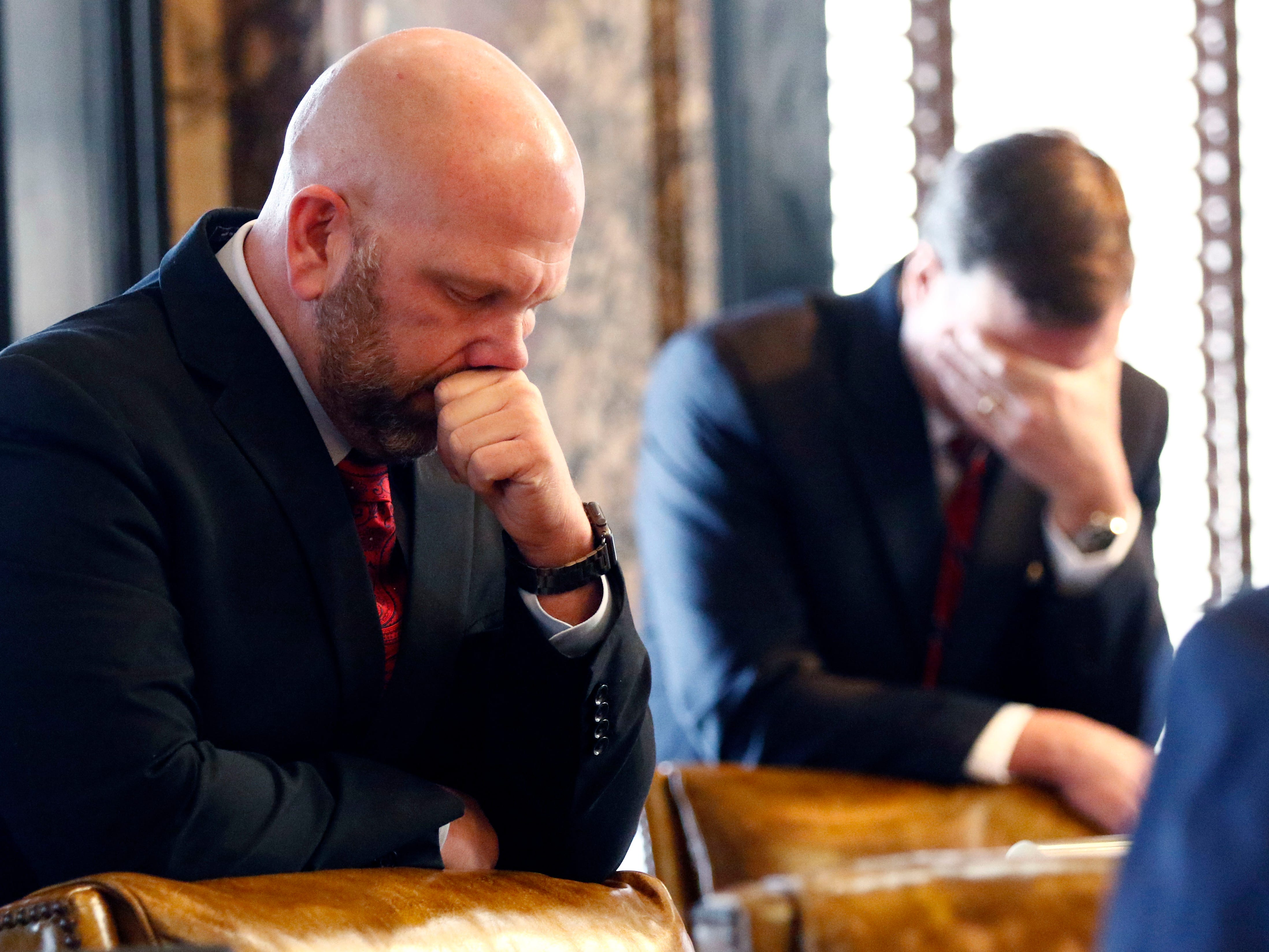 Republican Senators Chris Massey of Nesbit, left, and Walter Michel of Ridgeland, bow their heads and pray during the invocation to start the 2019 Mississippi legislative session at the Capitol in Jackson, Miss., Tuesday, Jan. 8, 2019.