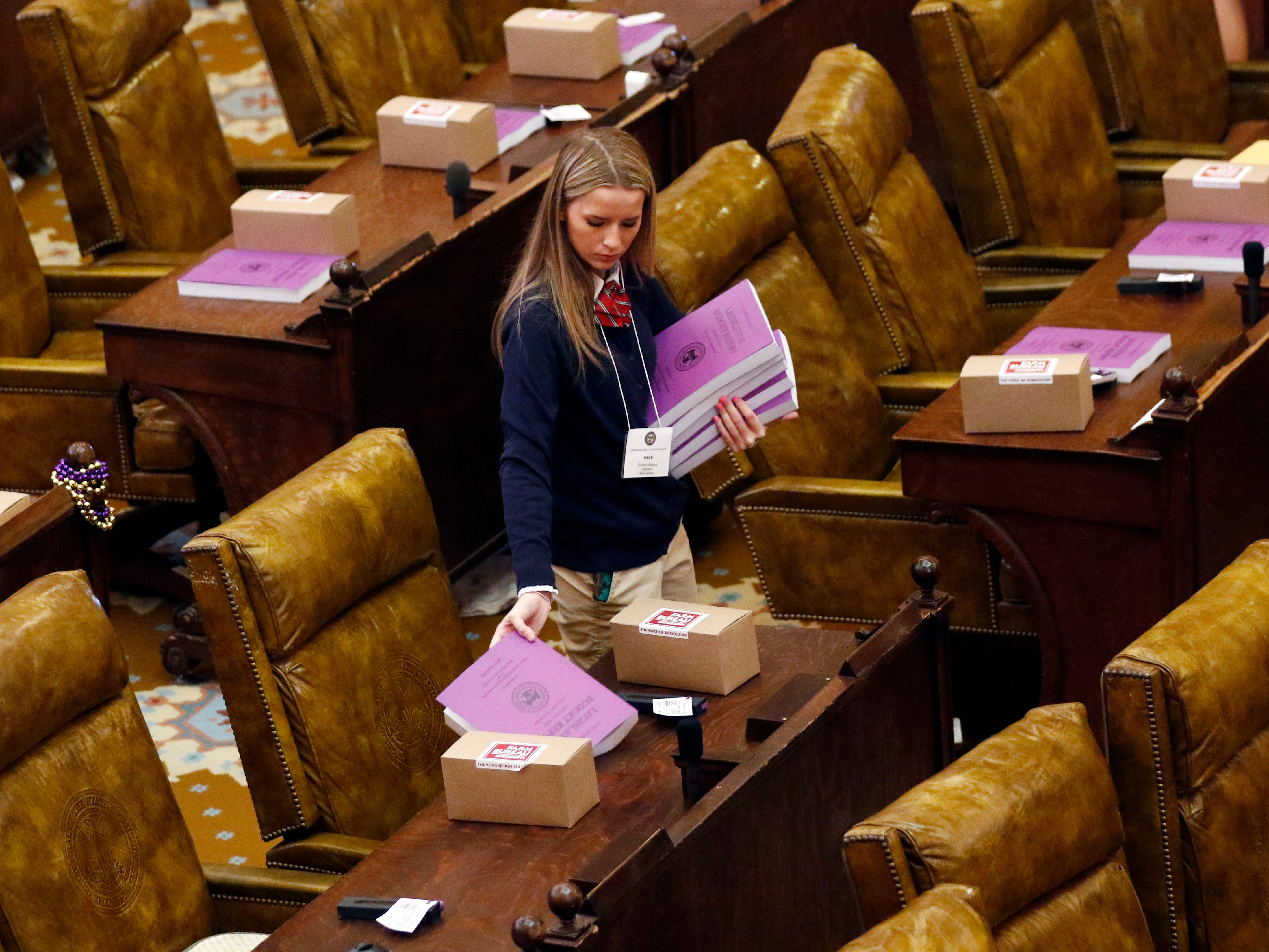 "A House page passes out individual copies of the Mississippi's fiscal year 2020 budget amid the boxes of ""swag"" given to lawmakers of both chambers, Tuesday, Jan. 8, 2019, prior to the start of the session.  2019 Mississippi legislative session at the Capitol in Jackson, Miss."