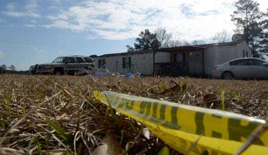 Pieces of crime scene tape are strewn on the lawn of Ericka Hall's house on Tuesday, Jan. 8, 2019, outside Magnolia, Miss., where the 32-year-old Pike County woman died allegedly at the hands of her 12- and 14-year-old daughters.