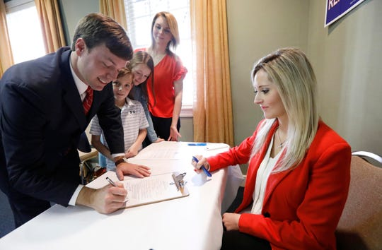 State Rep. Robert Foster, R-Hernando, left, signs a statement of intent to run for governor before Jennifer Dunagin, communications director of the Mississippi Republican Party, moments after announcing his candidacy for governor, Tuesday, Jan. 8, 2019, at the state GOP headquarters in Jackson, Miss. His son Hayes, 8, daughter Libby, 10, and wife Heather Foster watch.