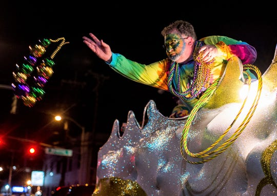 A costumed reveler throws Mardi Gras beads into a crowd of spectators during the Friday Night Parade in downtown Lafayette, Louisiana, on Feb. 13, 2015.