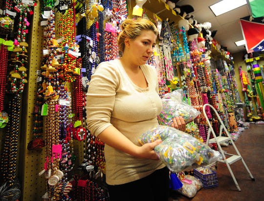 Store manager Megan Trahan sorts and stocks Mardi Gras beads at Beads Galore in Lafayette, Louisiana on  Feb. 5, 2014.