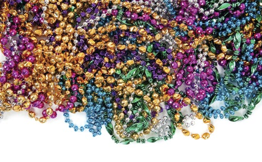 Mardi gras beads on white with copy space