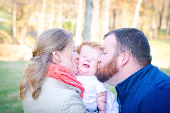 Ashey and Brady Gray kiss their daughter, Ainsley Grace.
