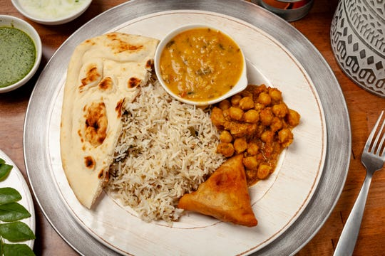 A picture of the vegetarian combo that you can find on Friday (Combo #1) at Cloves Indian Cafe in downtown, Lafayette. This combo includes Pulao Rice, Chole Masala, Sambhar Dal, and veggie samosa.