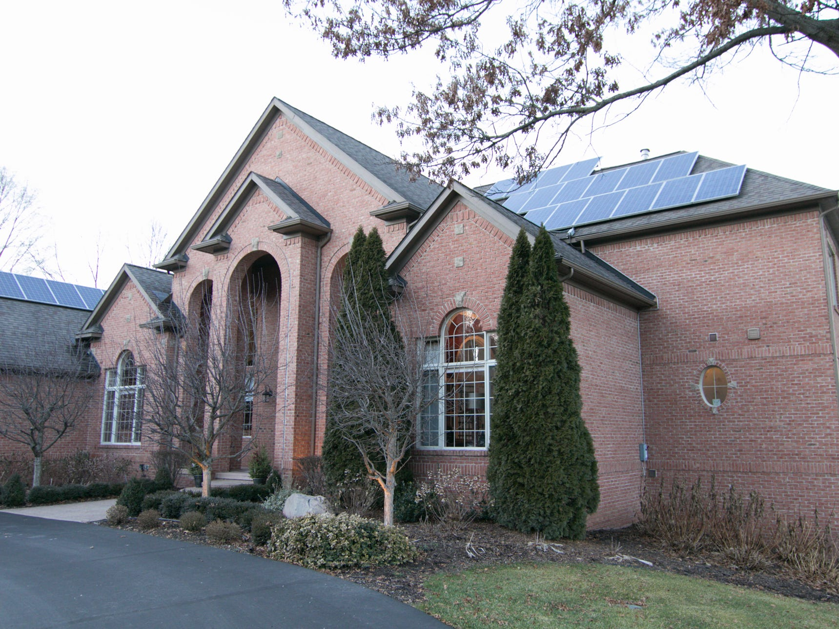 Solar panels facing east on the roof of Adam and Michelle Harris's Genoa Township home, shown Friday, Jan. 4, 2019, provide much of the electricity the large home uses.