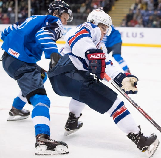 United States forward Logan Cockerill (12) of Brighton fights for the puck with Finland's Otto Latvala (21) during a world junior hockey championships game in Victoria, British Columbia on Monday, Dec. 31, 2018.