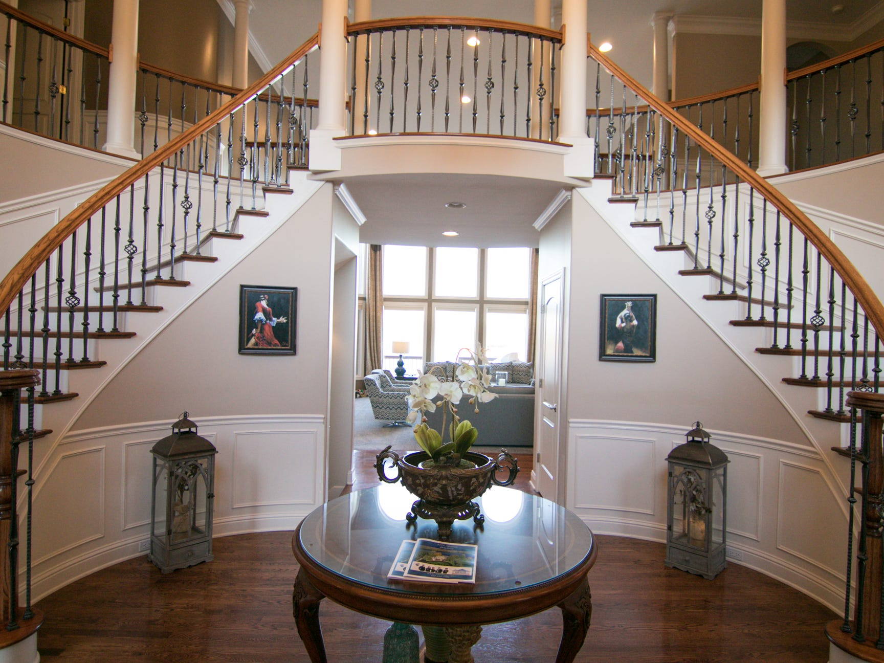A curved grand staircase is crowned with a curved balcony on the second floor of Adam and Michelle Harris's Genoa Township home, shown Friday, Jan. 4, 2019.