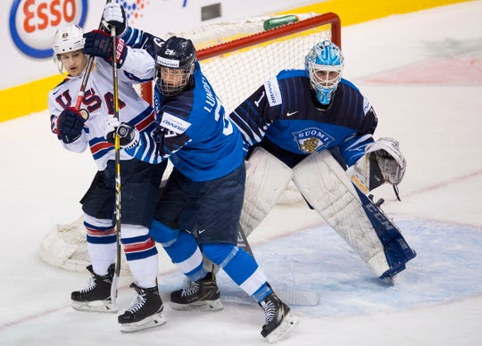 Finland's Anton Lundell (29) tries to clear United States forward Logan Cockerill of Brighton, left, from in front of goalie Ukko-Pekka Luukkonen during the gold medal game of the world junior hockey tournament on Saturday, Jan. 5, 2019 in Vancouver, British Columbia.