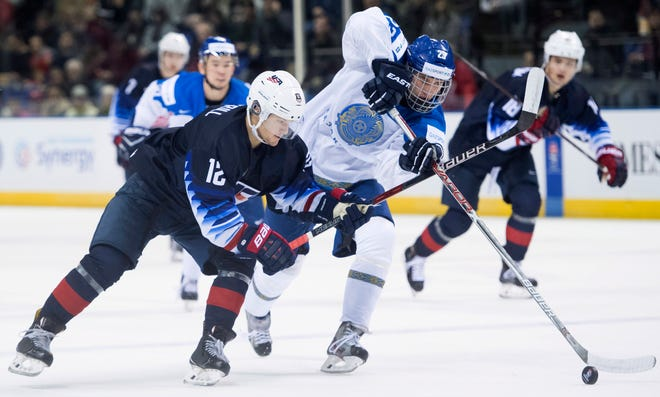 United States' Logan Cockerill (12) of Brighton fights for control of the puck with Kazakhstan's David Muratov (23) during a world junior hockey championships game in Victoria, British Columbia on Friday, Dec. 28, 2018.