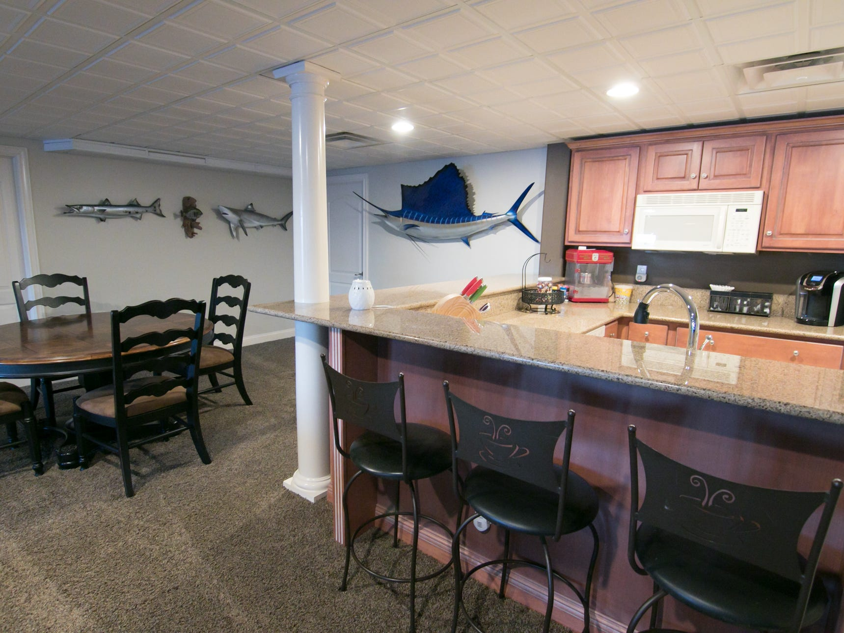 The basement of Adam and Michelle Harris's Genoa Township home features a second kitchen and displays some of Adam's prize catches on the wall, shown Friday, Jan. 4, 2019.