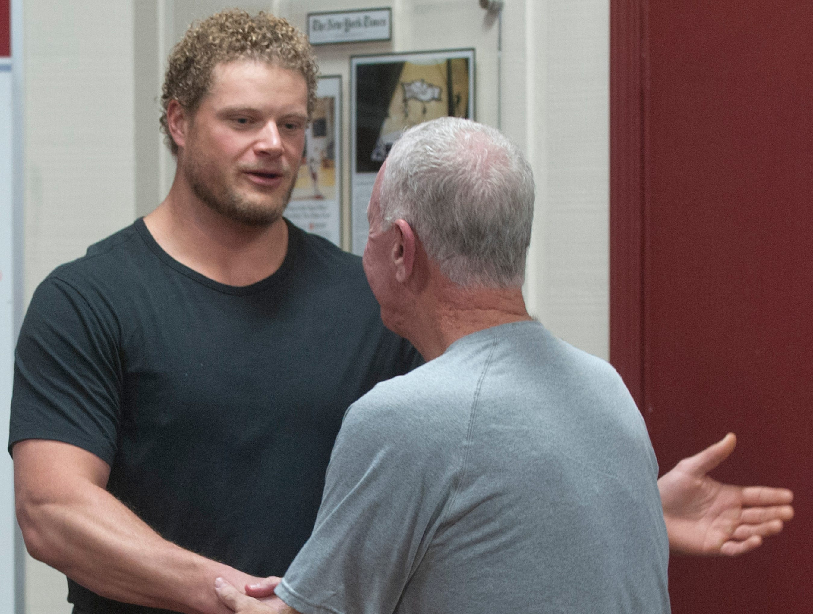 Former Buffalo Bills center and University of Louisville football player Eric Wood is thanked by Bellarmine head basketball coach Scott Davenport after Davenport introduced him to the team in the locker room following practice. Wood was at the school to give an inspirational talk to the players.18 December 2018