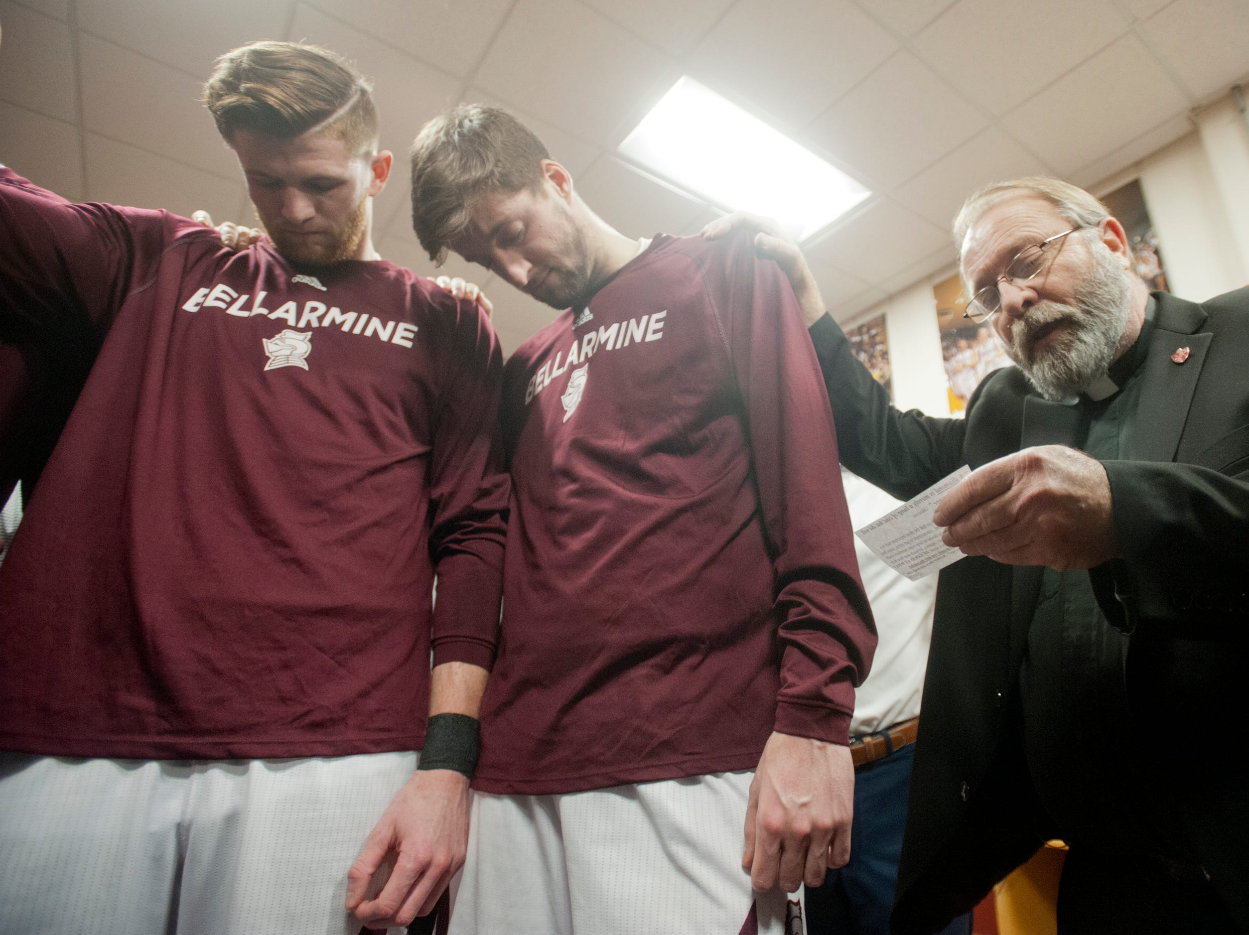 At the end of the final pre-game meeting, Father Dale Cieslik, chaplain for the Bellarmine Basketball team for the past 14 years, says a prayer with the team. At left are Bellarmine forward Ben Weyer and Bellarmine forward Ethan Claycomb .18 December 2018