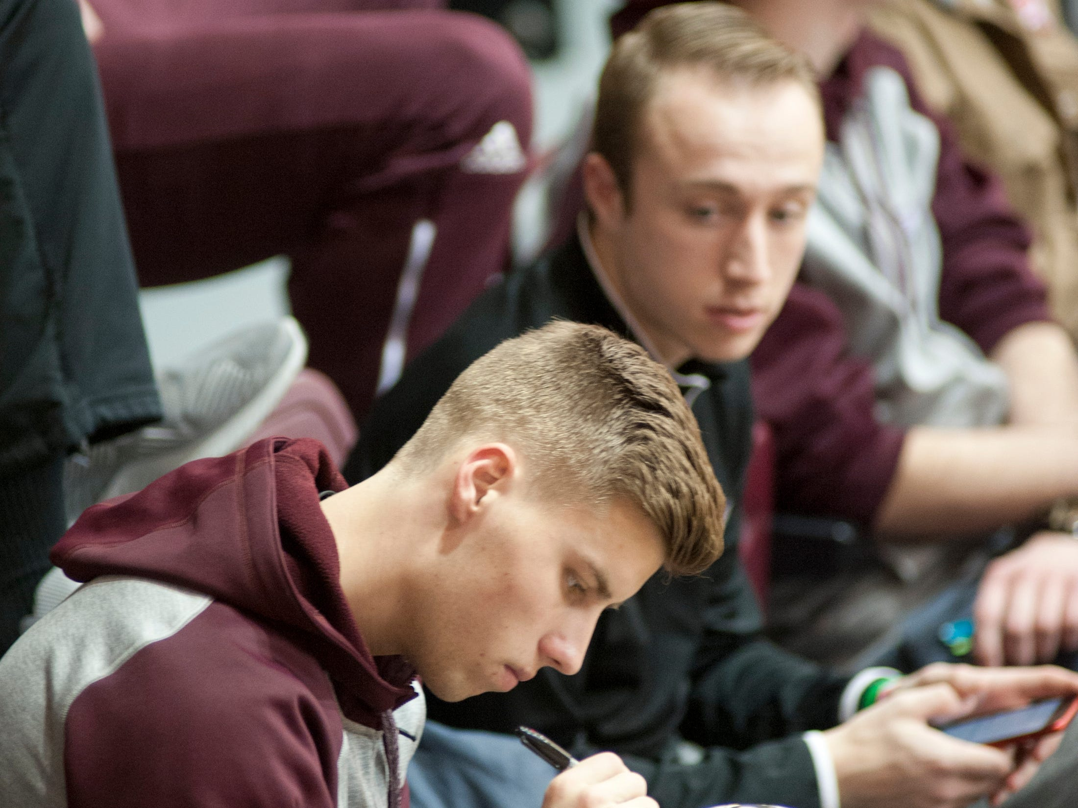 Bellarmine guard Juston Betz and his teammates sign a basketball for a staffer's son's birthday present as the team watches the first game of the Bellarmine Classic basketball tournament from the bleachers.18 December 2018