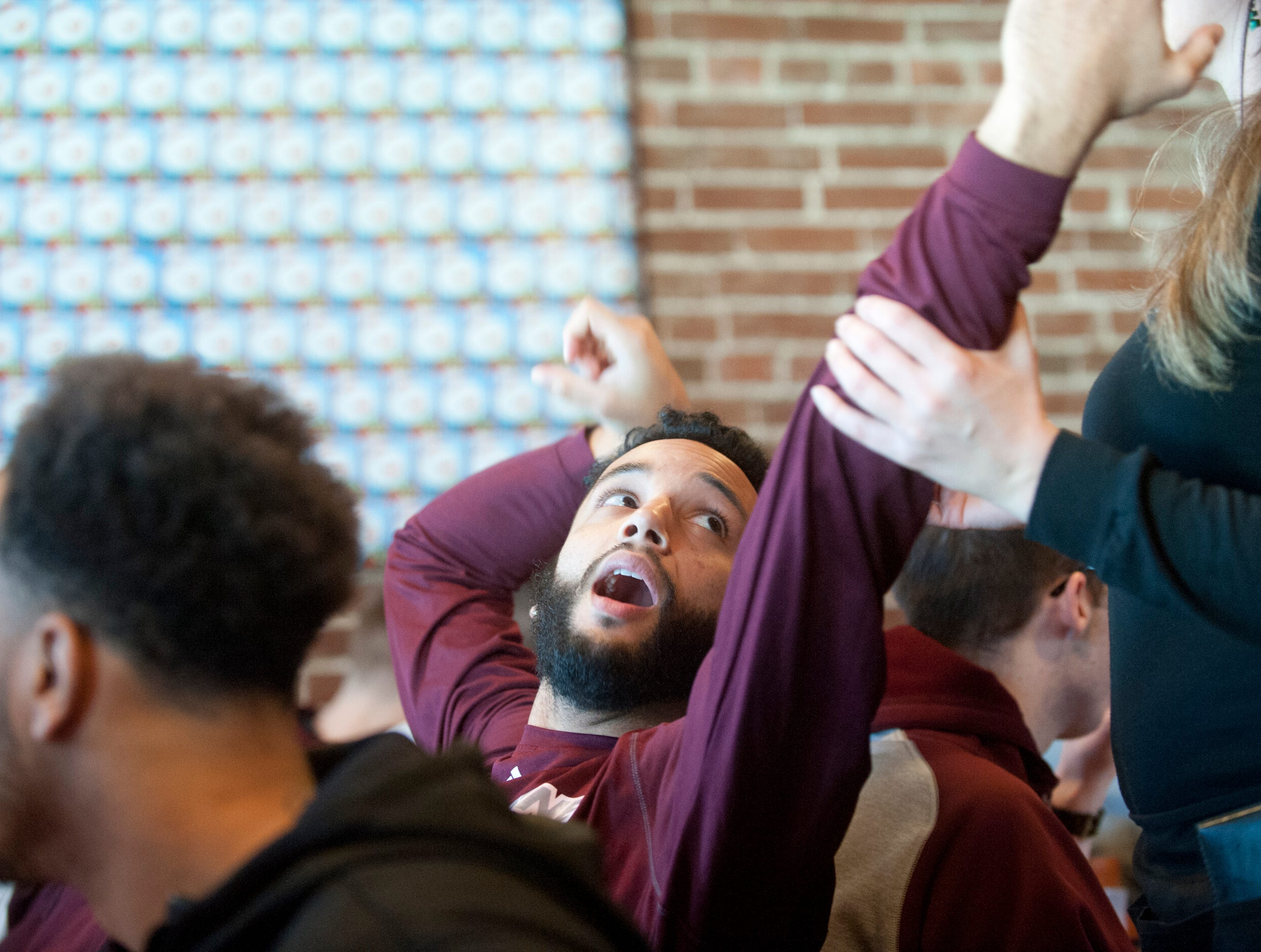 Bellarmine guard Tyler Jenkins, while stretching his arms, bumps into the waitress and reacts to the contact.14December 2018