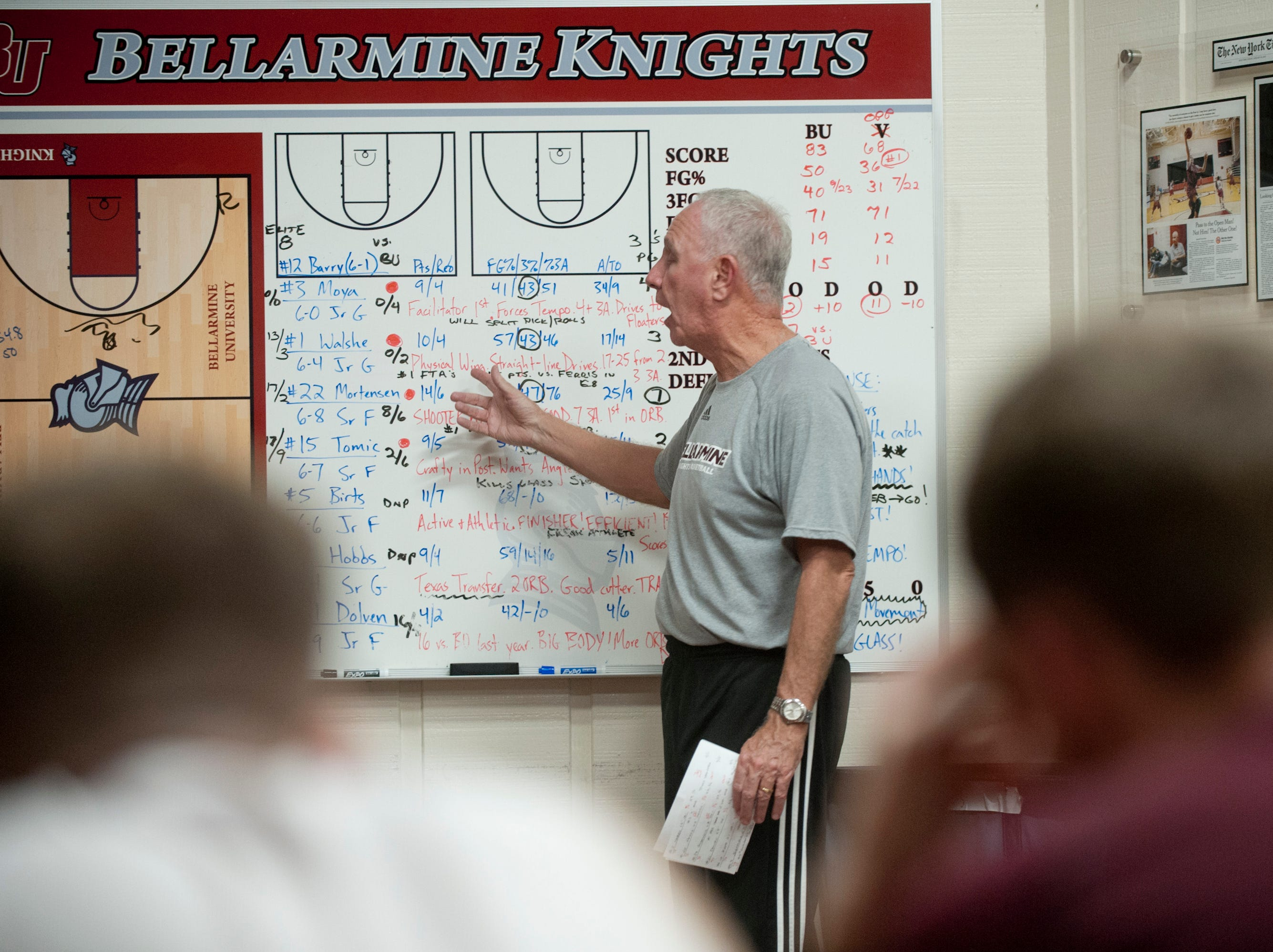 With the stat of all the opposing players displayed on a whiteboard behind him, Bellarmine head basketball coach Scott Davenport preps his team during a pre-game meeting in the locker room.18 December 2018