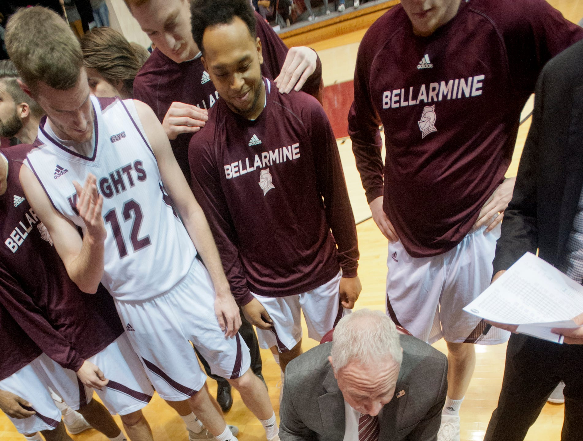 At the start of the second half of play, Bellarmine head basketball coach Scott Davenport huddles with his players as he maps out plan of action on his clipboard.18 December 2018