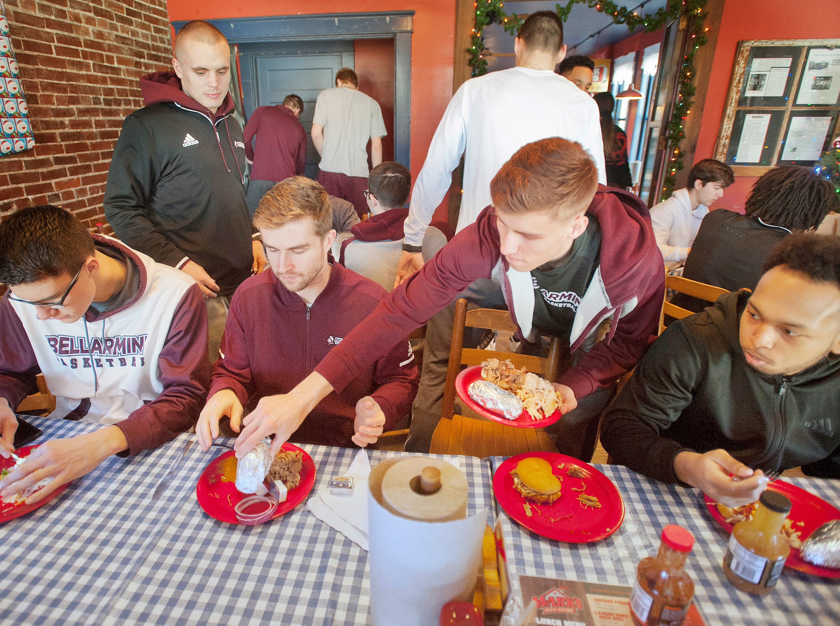 Bellarmine guard Juston Betz, center right, puts a baked potato on the plate of teammate forward Skyler Hunter, center left. The team was eating together at Mark's Feed Store on Bardstown Road.14December 2018