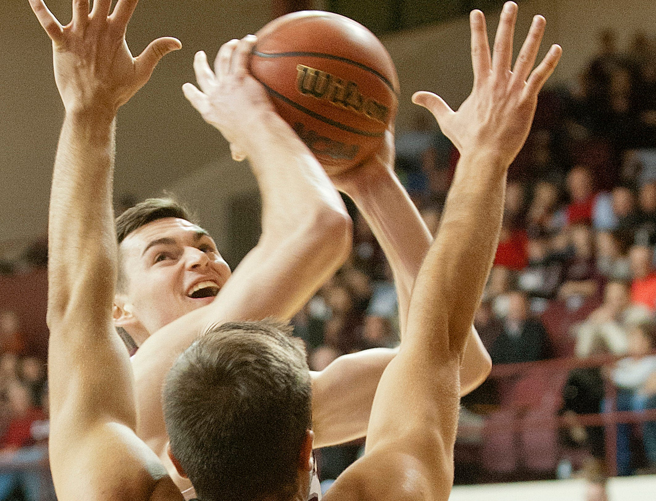 Bellarmine guard-forward Alex Cook  drives to the basket and passed the outstretched arms of Barry's forward Marko Tomic.18 December 2018
