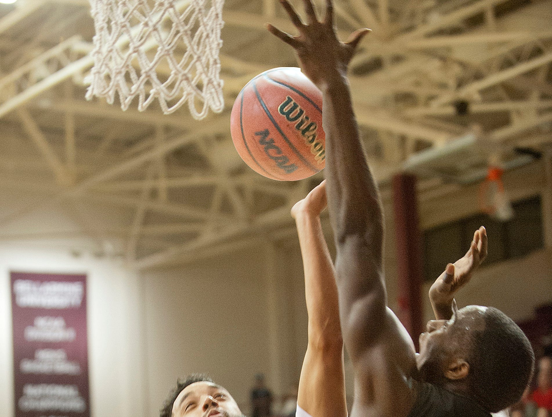 Bellarmine guard Tyler Jenkins  tries to tap in the ball as the basket is defended by Barry forward Tylan Birts.18 December 2018