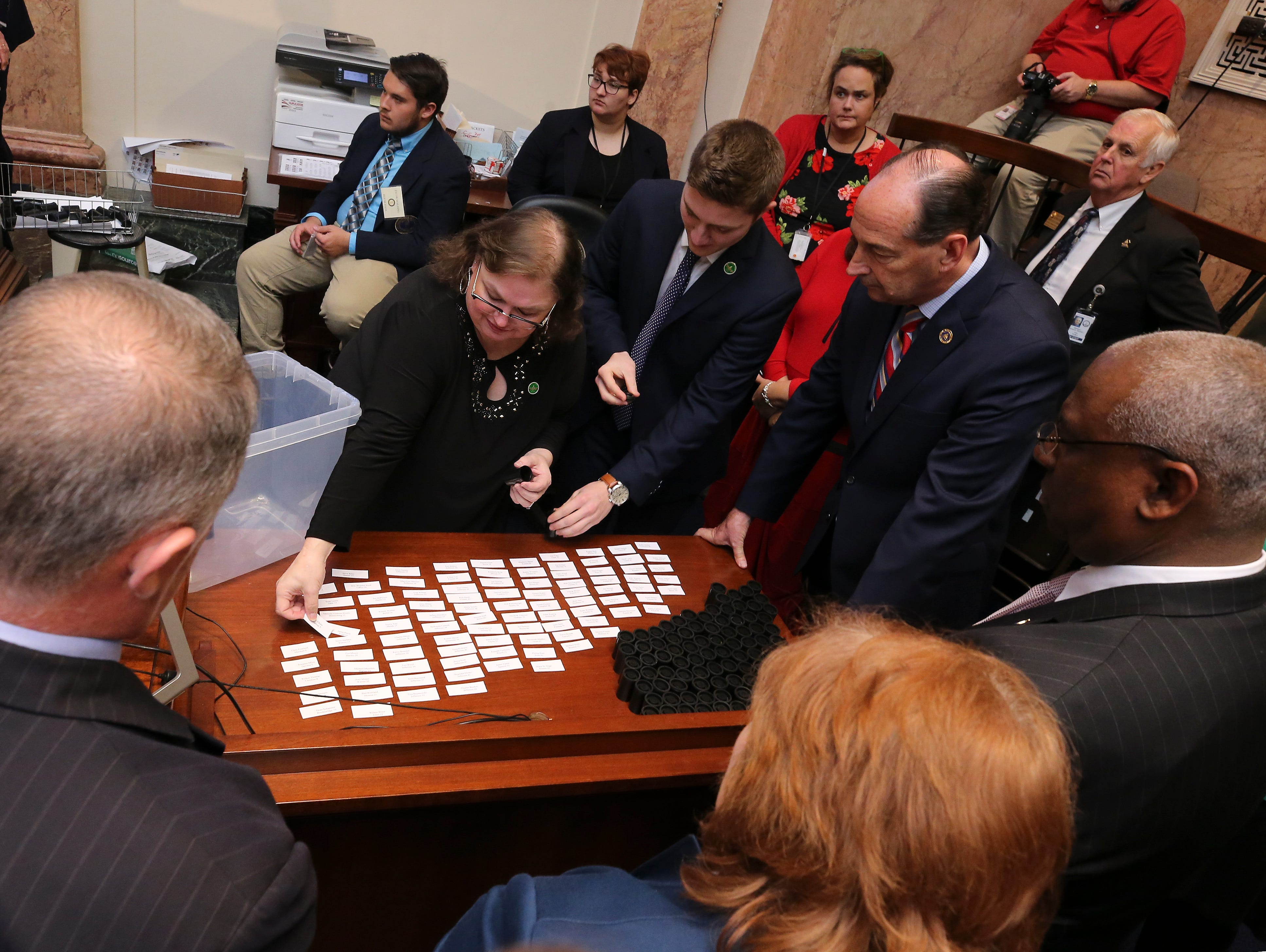 House clerk Melissa Bybee-Fields, center, laid out the names of House members to create a committee on committees to decide how to proceed on ruling of the disputed House seat for Jim Glenn who was elected to the House seat for Owensboro by one vote.  After placing the names in cannisters, she randomly selected them to form the committee. Jan. 8, 2019
