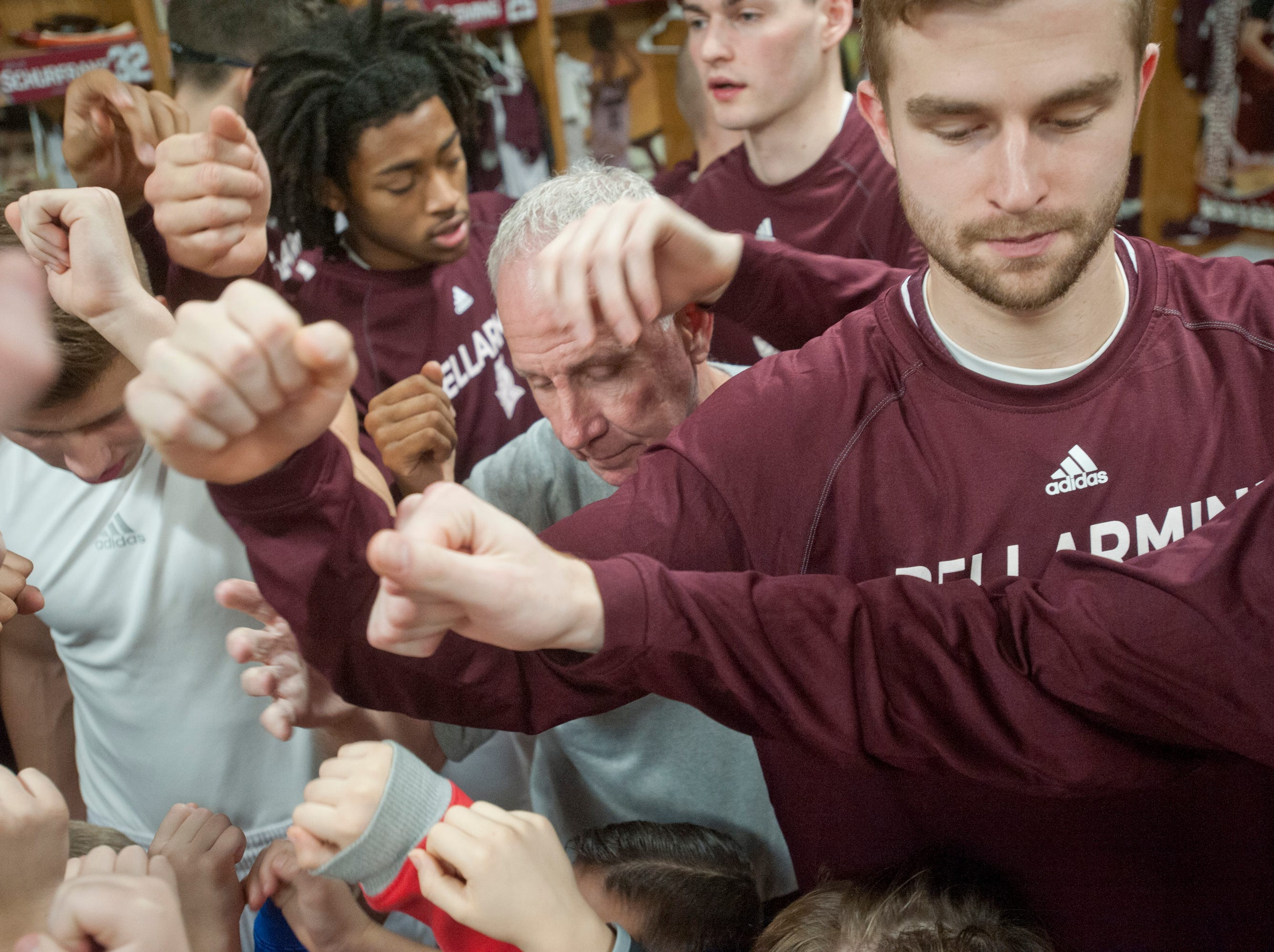 Bellarmine head basketball coach Scott Davenport joins hands with his team at the end of the meeting.18 December 2018