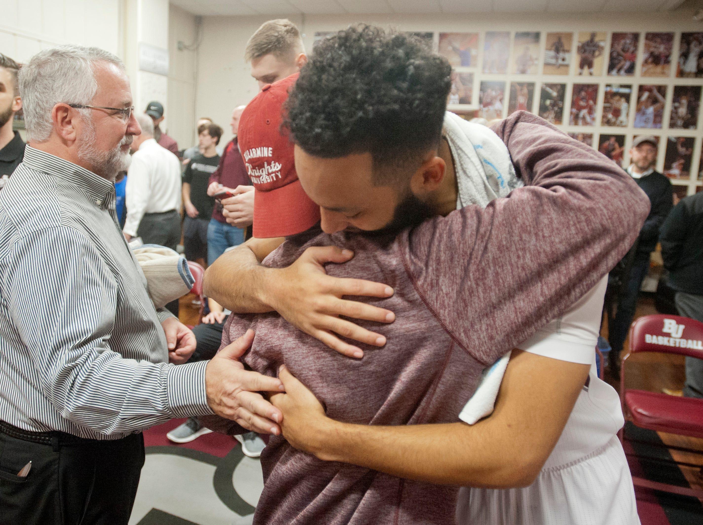 McSweeney gets a warm embrace from Bellarmine guard Tyler Jenkins. At left is team trainer Brad Bluestone.14December 2018