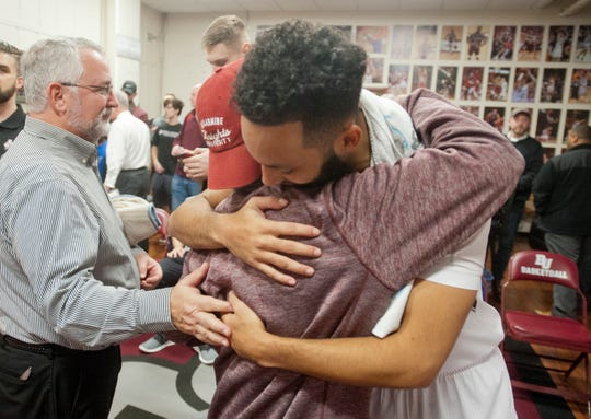 Patrick McSweeney gets a warm embrace from Bellarmine guard Tyler Jenkins. At left is team trainer Brad Bluestone