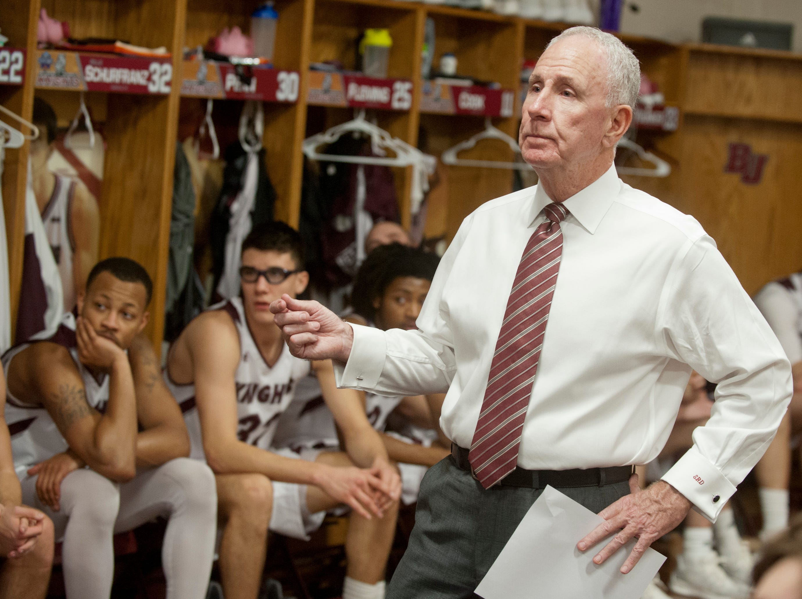 After the game, Bellarmine head basketball coach Scott Davenport reviews his team's performance in the locker room.18 December 2018