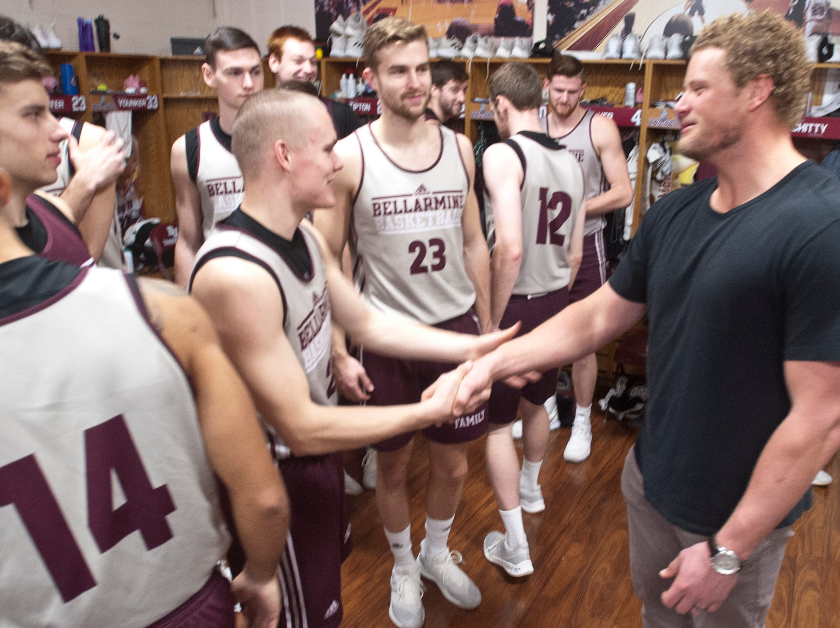 Former Buffalo Bills center and University of Louisville football player Eric Wood takes his turn shaking hands with Bellarmine guard C.J. Fleming in the locker room aftr Wood gave the basketball team an inspiring talk following the team's afternoon practice.18 December 2018