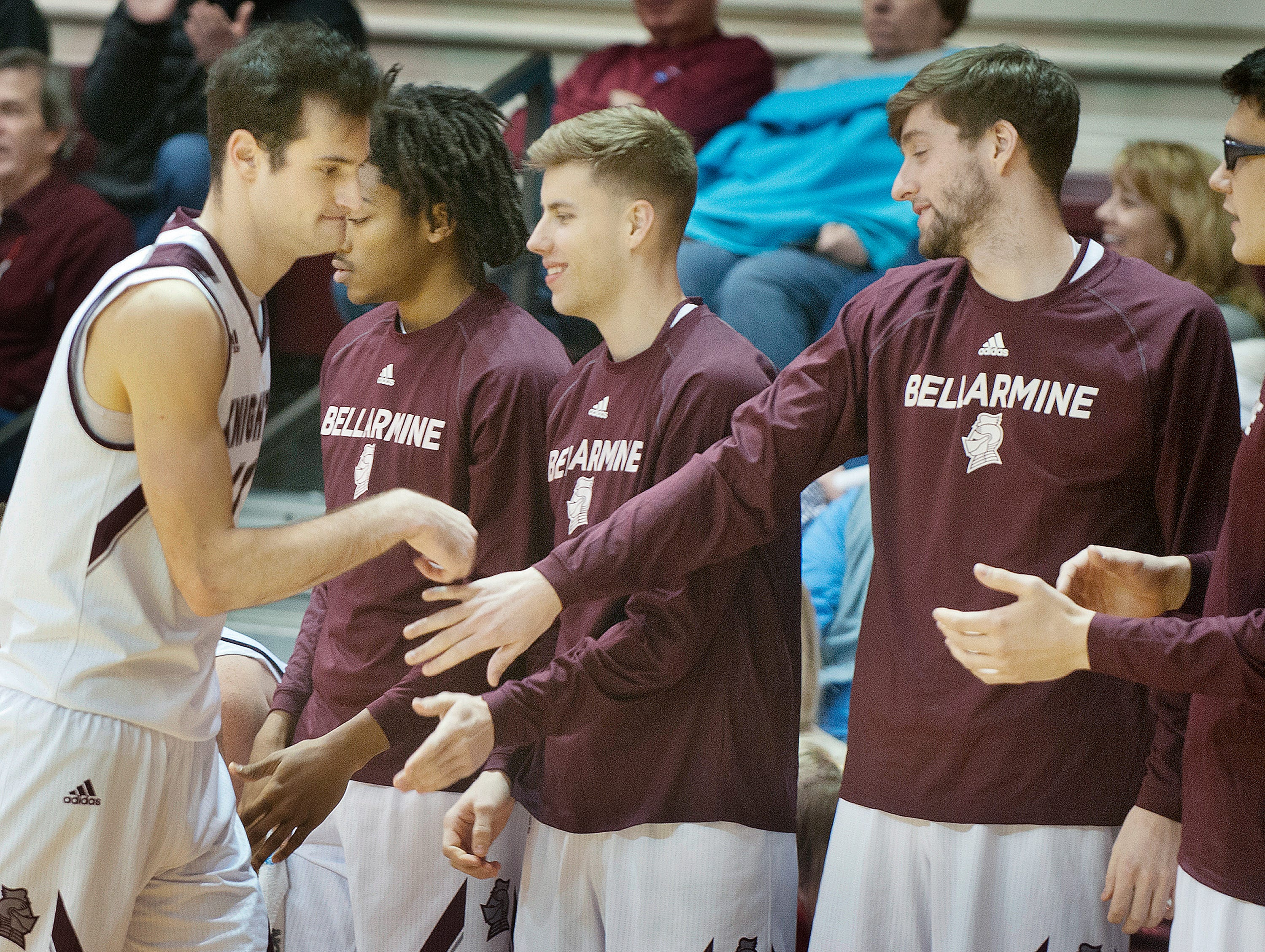Bellarmine forward Adam Eberhard raps the hands of players in camaraderie after coming out of the game late in the second half.18 December 2018