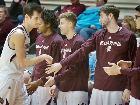 Bellarmine forward Adam Eberhard raps the hands of players in camaraderie after coming out of the game late in the second half.