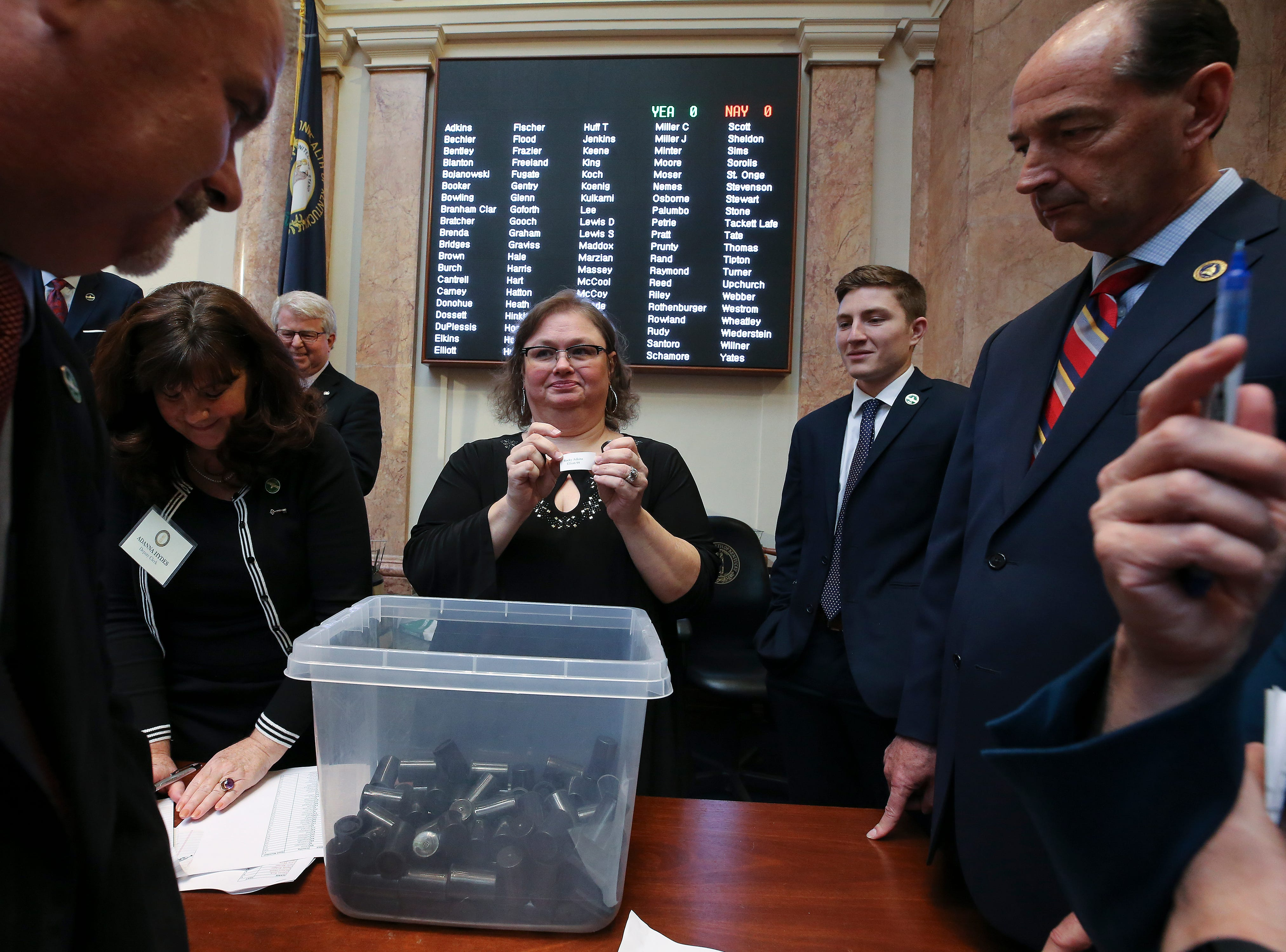 House clerk Melissa Bybee-Fields, center, randomly pulled a name from a bin of House members to create a committee on committees to decide how to proceed on ruling of the disputed House seat for Jim Glenn who was elected to the House seat for Owensboro by one vote.  Coincidentally she pulled Rep. Rocky Adkins name during this selection as he watched the process on the right.  Rep. Bam Carney, left, was also selected.Jan. 8, 2019