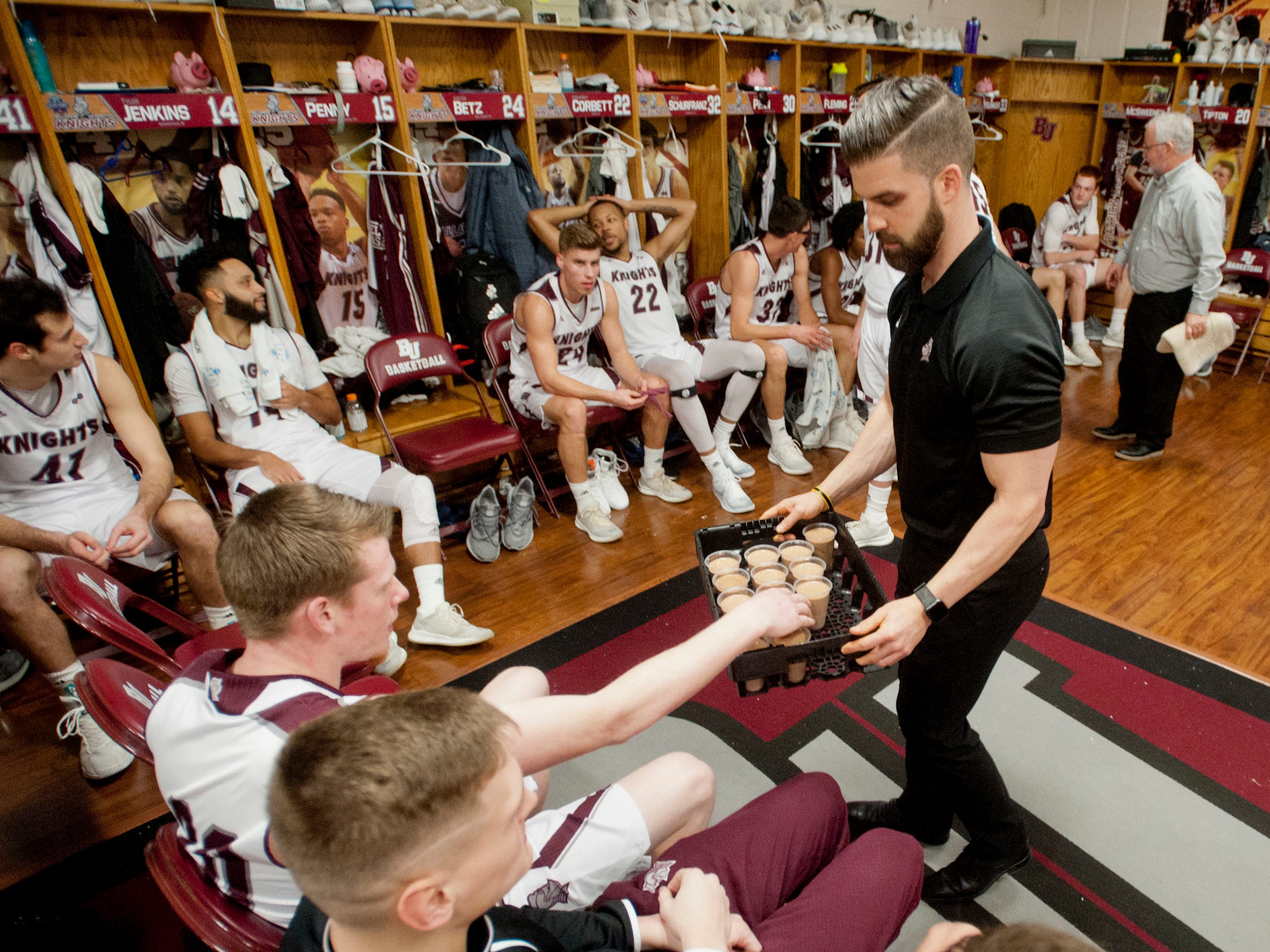 After the game, team strength coach Steve Hartman hands out protein shakes to the players.18 December 2018