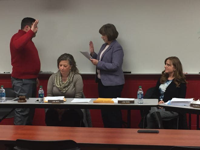 Shelby school board president Scott Rose is sworn in Monday by Treasurer Elizabeth Anatra. Board members Lorie White (l) and Lynn Friebel are seated.
