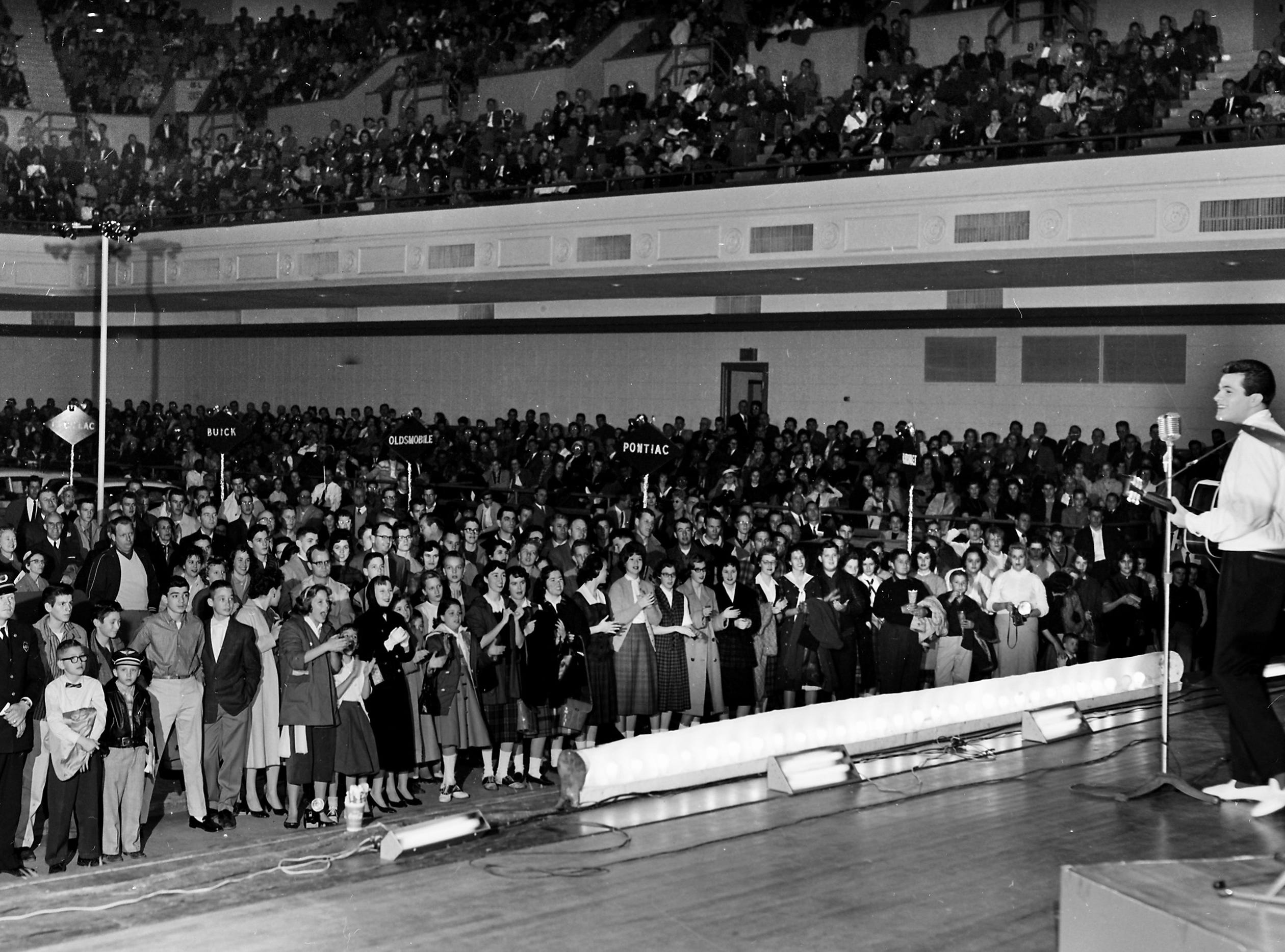 Enthralled fans, so packed that even standing room was taken, crowded close to hear singing celebrity Tommy Sands rock with a tune during the Memphis Auto Show in Ellis Auditorium on 10 Jan 1959.  He was scheduled for three performances  before the exhibit closed.