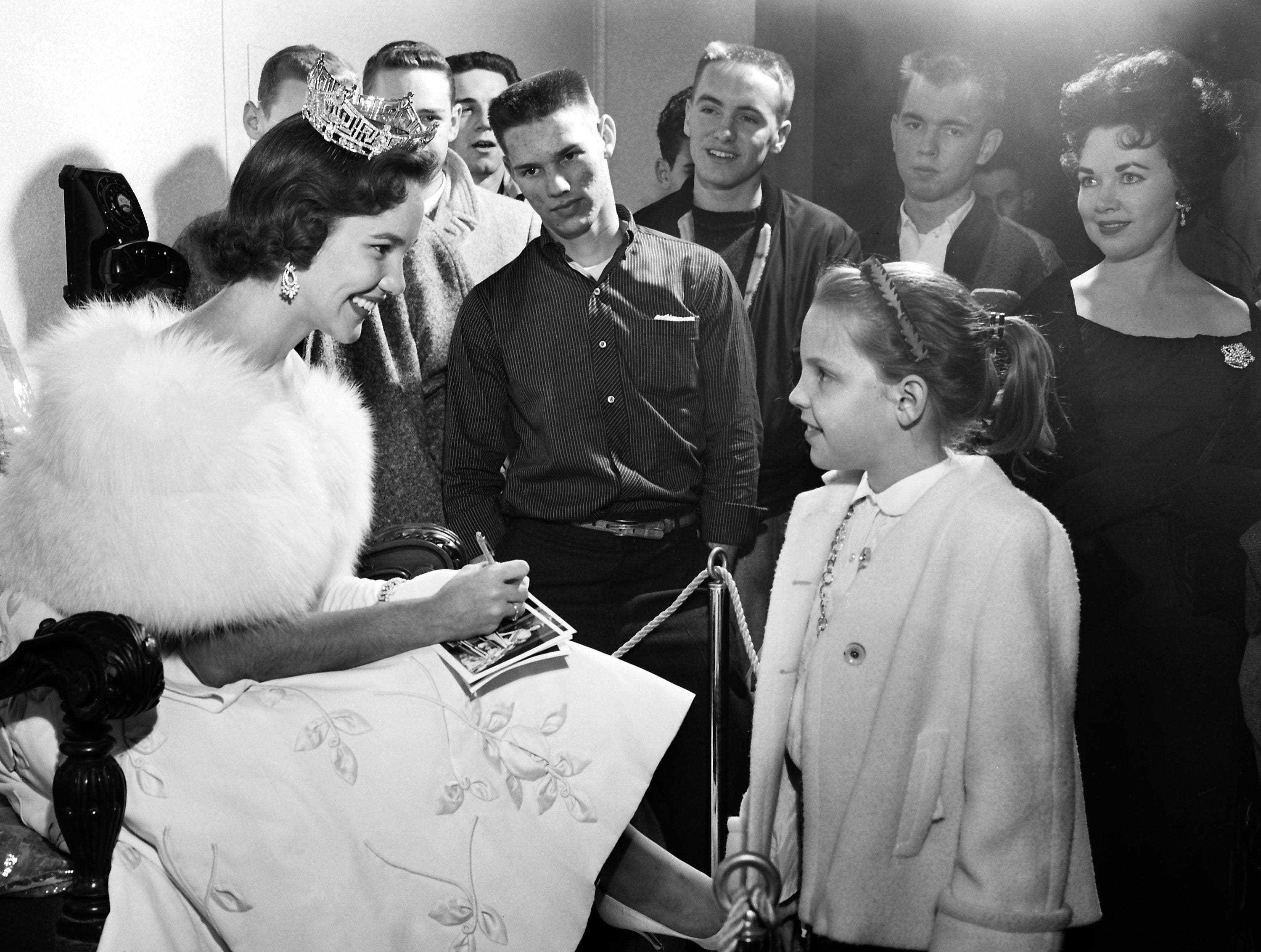 Autographing pictures of herself was nearly a full-time job for Miss America on 11 Jan 1959 at the Memphis Auto Show in Ellis Auditorium.  Drue Bauer, 10, daughter of Mr. and Mrs. Fred Bauer of 2929 Iroquois, was one of the lucky autograph seekers who took home the signature of Mary Ann Mobley, the 1959 national beauty queen from Brandon, Ms.
