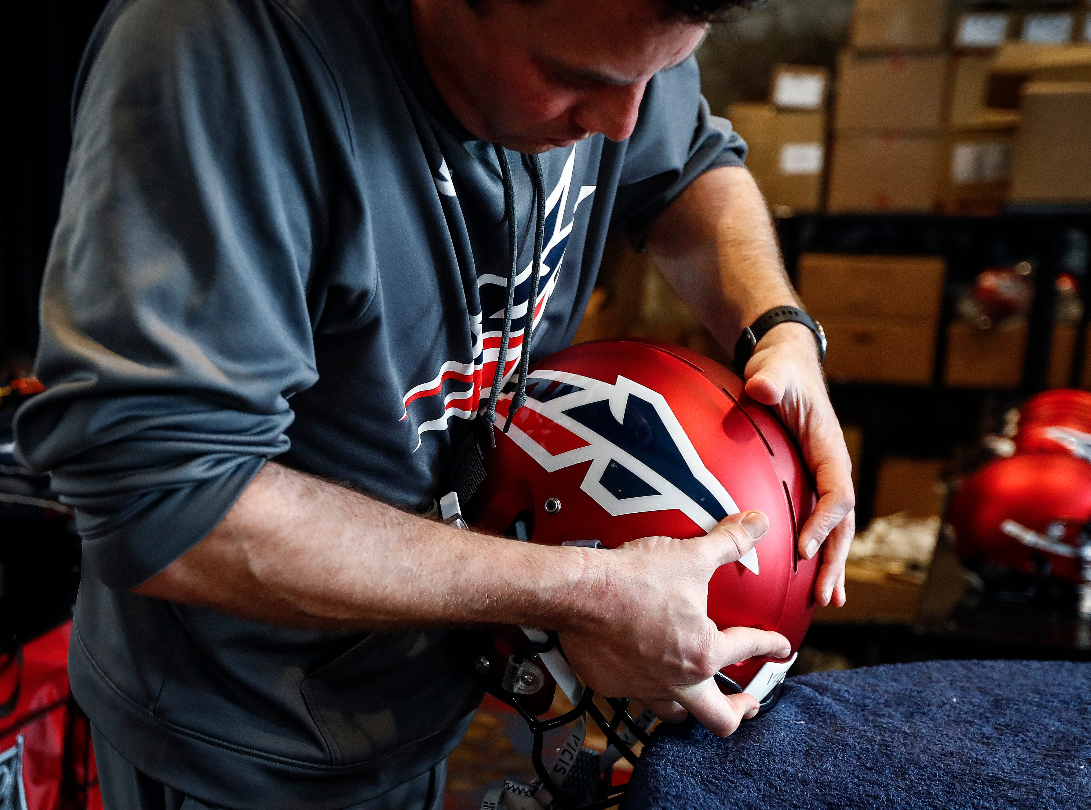 Memphis Express equipment manager Jeff Bower places decals on new helmets during training camp in San Antonio, Texas.