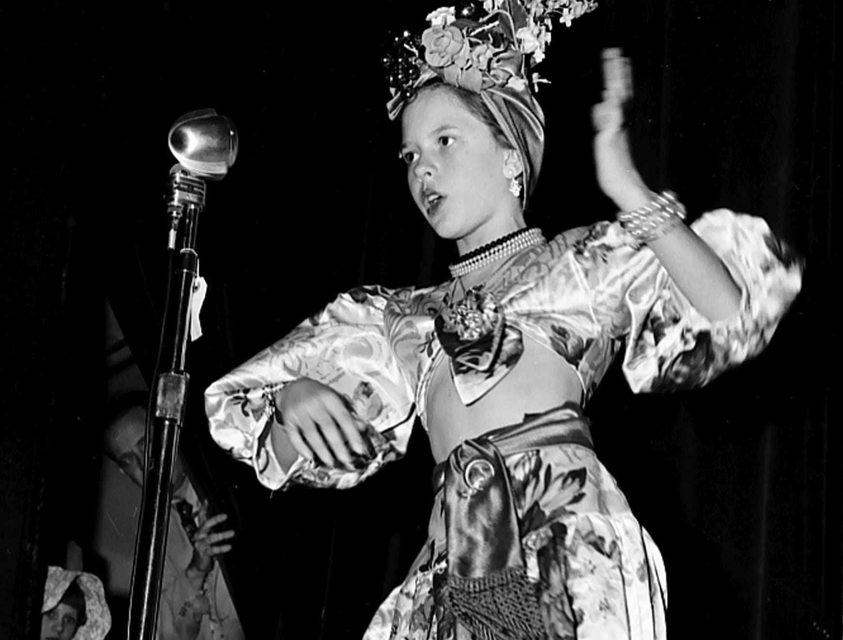 Swinging hips to a Latin rhythm in February 1951 is this turbaned little replica of Carmen Miranda — pretty Sonja Bailey of Peabody School. Sonja was one of the entries in a Kiwanis Club sponsored party at Linden Circle Theater for Safety Council patrol members.