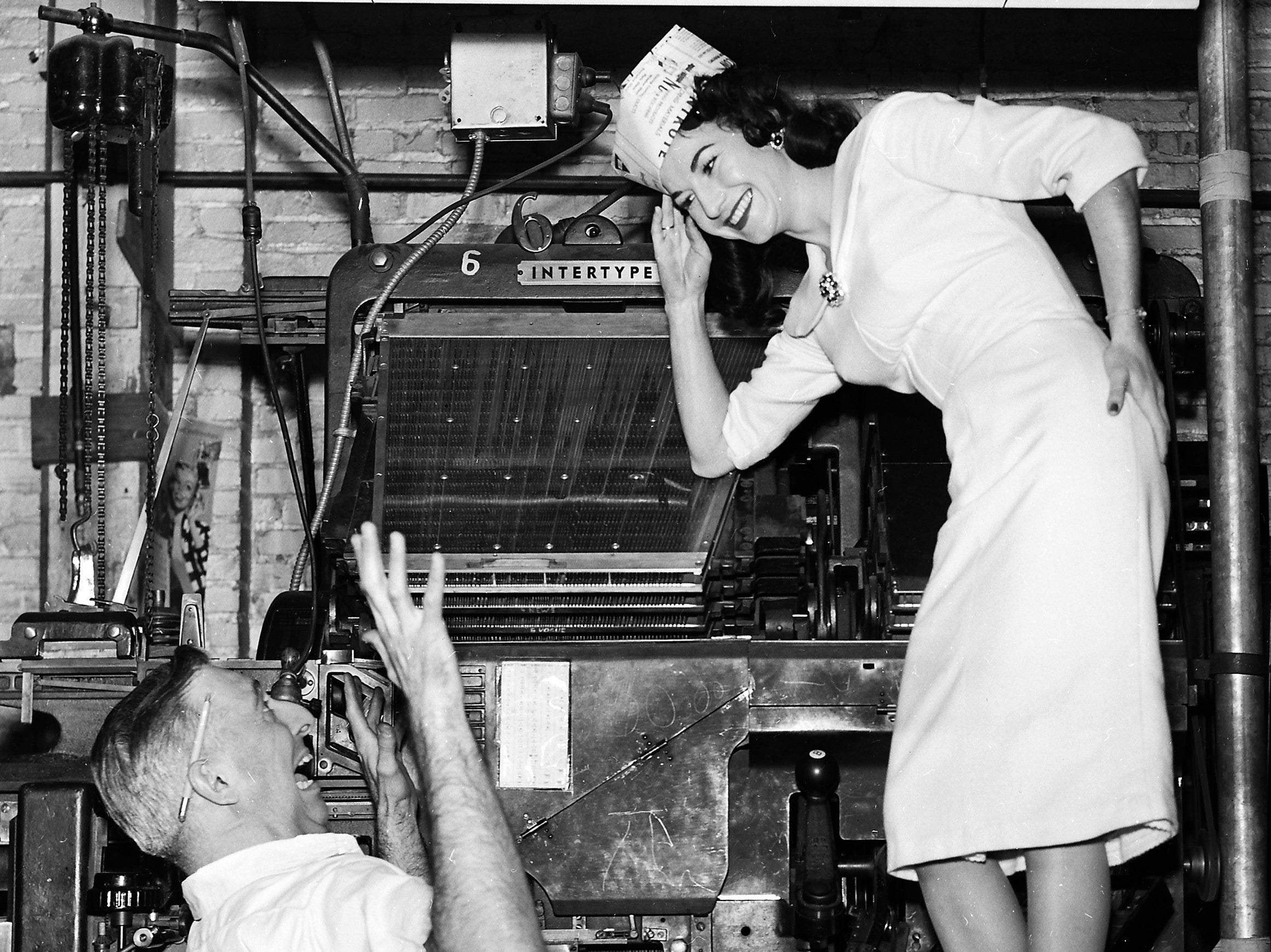 Pleasantly startled was Vince Barba of 138 South Marne when he looked up from his typesetting machind on 9 Jan 1959 to see Miss Edith Smith of 170 North Hollywood saluting him.  She's Miss Printer's Devil for Printing Week Jan 11-17.